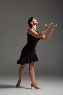 elegant, sensual dancer in black dress performing tango with closed eyes on grey background