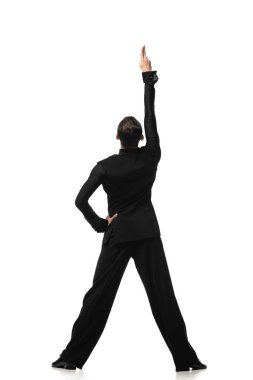 back view of dancer in elegant black suit performing tango with hand on hip on white background