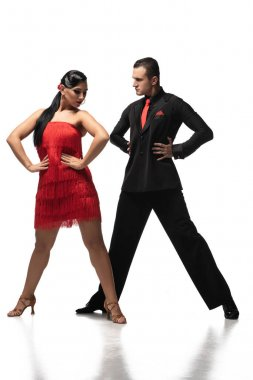 stylish couple of dancers holding hands on hips while performing tango on white background
