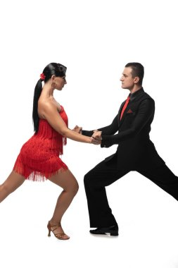 passionate, elegant dancers looking at each other and holding hands while performing tango on white background