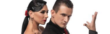 panoramic shot of handsome, elegant dancer looking at camera while performing tango with beautiful partner isolated on white