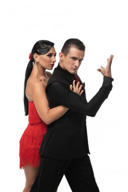 handsome, elegant dancer looking at camera while performing tango with beautiful partner isolated on white