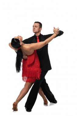 handsome, elegant dancer leading attractive partner while performing tango on white background