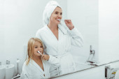 happy mother and daughter in bathrobes brushing teeth near mirror