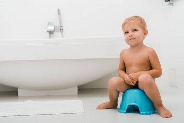 adorable toddler boy sitting on blue potty near bathtub