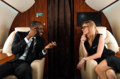 happy african american businessman pointing with finger while looking at businesswoman in private jet