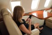 podnikatelka pomocí smartphone s prázdnou obrazovkou v soukromém letadle