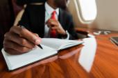 levágott kilátás afro-amerikai férfi gazdaság toll mellett notebook privát jet
