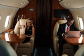 african american businessman using laptop near businesswoman talking on smartphone in private jet