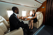 happy african american businessman gesturing near businesswoman in private plane