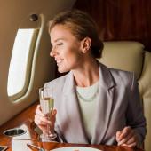 fröhliche Geschäftsfrau mit Champagnerglas im Privatjet