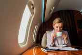 cheerful businesswoman holding cup while reading business newspaper in private plane