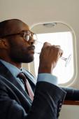 jóképű afro-amerikai üzletember szemüvegben pezsgőt iszik magánrepülőn