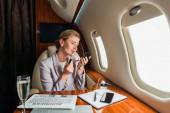 atraktivní podnikatelka nanášení lesk na rty v soukromém letadle