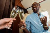 selektivní zaměření šťastný mezirasový pár cinkání šampaňské brýle v soukromém letadle