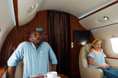 Fotografie scared african american man and woman with fear of flight in private plane