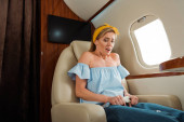 Fotografie scared woman with fear of flight touching safety belt in private plane