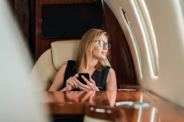 Selective focus of attractive businesswoman in glasses holding smartphone in private jet stock vector