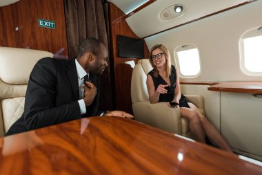 Selective focus of cheerful businesswoman and african american businessman in private jet stock vector