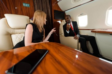 Selective focus of businesswoman pointing with finger near african american businessman in private jet stock vector