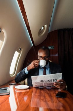 African american businessman in glasses reading business newspaper while drinking coffee in private plane stock vector
