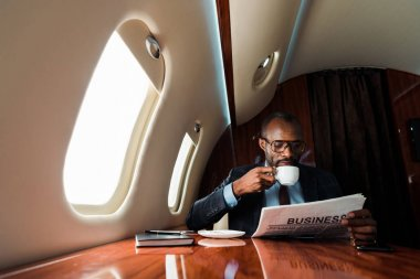 African american businessman reading business newspaper while drinking coffee in private plane stock vector