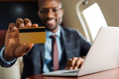 Selective focus of african american businessman holding credit card near laptop in private plane stock vector