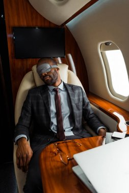 African american businessman with sleeping mask sitting in private plane stock vector