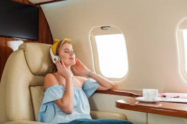 Happy woman listening music near cup with drink in private plane stock vector