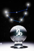 crystal ball with Capricorn zodiac sign isolated on black with constellation