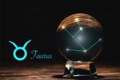 Kristallkugel mit Sternbild nahe Stier Tierkreiszeichen auf Holztisch isoliert auf schwarz