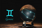 crystal ball with constellation near Gemini zodiac sign on wooden table isolated on black