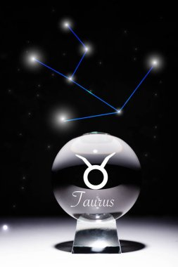 Crystal ball with Taurus zodiac sign isolated on black with constellation stock vector