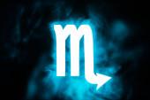 blue illuminated Scorpio zodiac sign with smoke on background