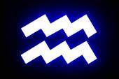 blue illuminated Aquarius zodiac sign isolated on black