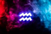 blue illuminated Aquarius zodiac sign with colorful smoke on background