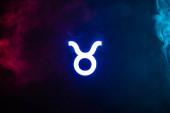 blau beleuchtetes Taurus Tierkreiszeichen mit buntem Rauch auf Hintergrund