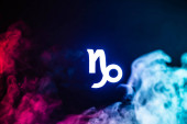 blau beleuchtetes Tierkreiszeichen Steinbock mit buntem Rauch auf Hintergrund