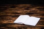 otevřít prázdnou knihu na dřevěném tvarovaném stole
