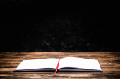 open book with red bookmark on wooden table