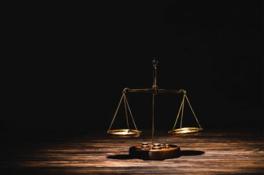 Golden scales of justice on wooden table on black background stock vector