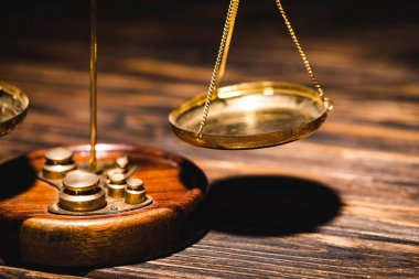 close up view of golden scales of justice on wooden table on black background