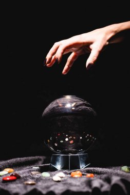 Cropped view of fortuneteller hand above crystal ball with fortune telling stones on black velvet cloth isolated on black stock vector