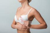 abgeschnittene Ansicht einer jungen Frau in weißem BH mit rosa Schleife als Brustkrebsbewusstsein isoliert auf grau