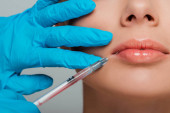 cropped view of beautician in latex gloves holding syringe near lips of girl isolated on grey