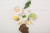 Top view of tzatziki sauce with ingredients on white wooden background
