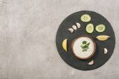 Top view of tzatziki sauce with vegetable and lemon slices on board on stone background