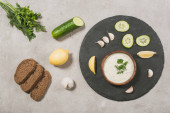 Top view of tzatziki sauce with ingredients and bread on stone background