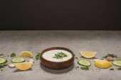 Tasty tzatziki sauce in wooden bowl with ingredients and spices on stone surface on black background