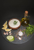 Homemade tzatziki sauce with ingredients, spices and olive oil on dark board on black background